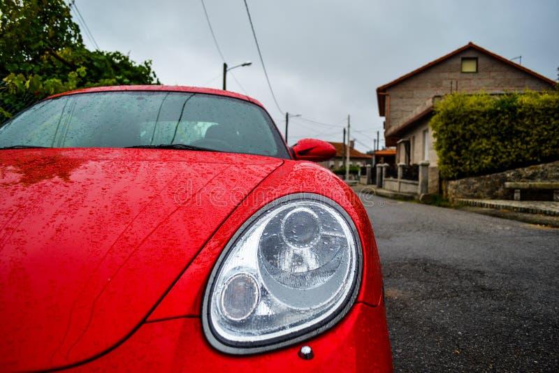 Voorlicht van rood Porsche Cayman 2 sportwagen 7, in a wordt geparkeerd die stock fotografie