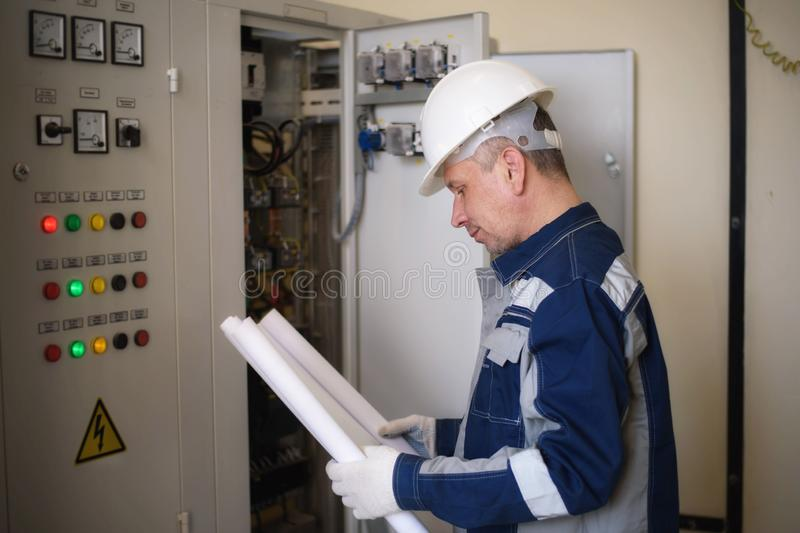 Voormanelektricien naast het dashboard Energie en elektrische veiligheid stock foto's
