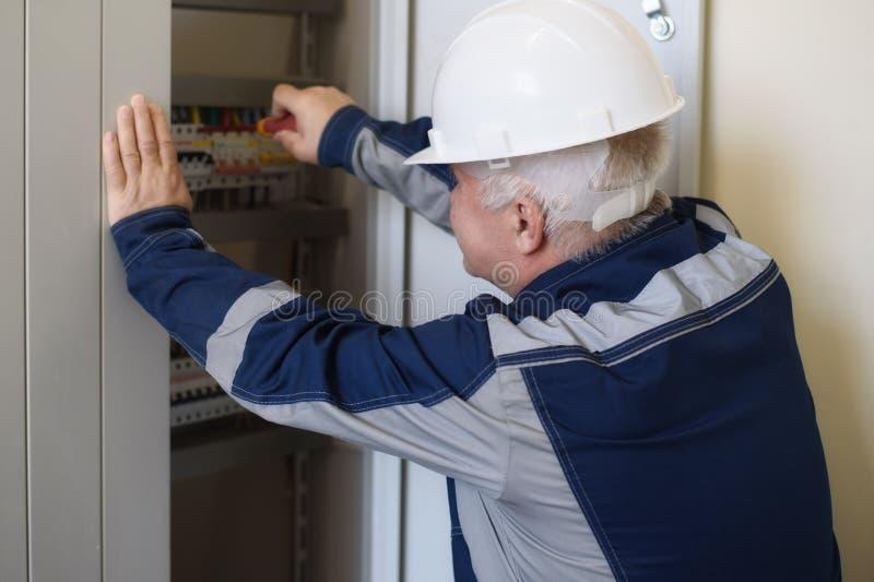 Voormanelektricien naast het dashboard Energie en elektrische veiligheid stock fotografie
