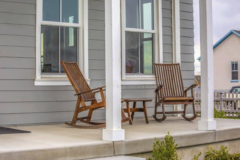Voorportiek van een huis met bruine schommelstoelen en rechthoekige witte pijlers stock fotografie