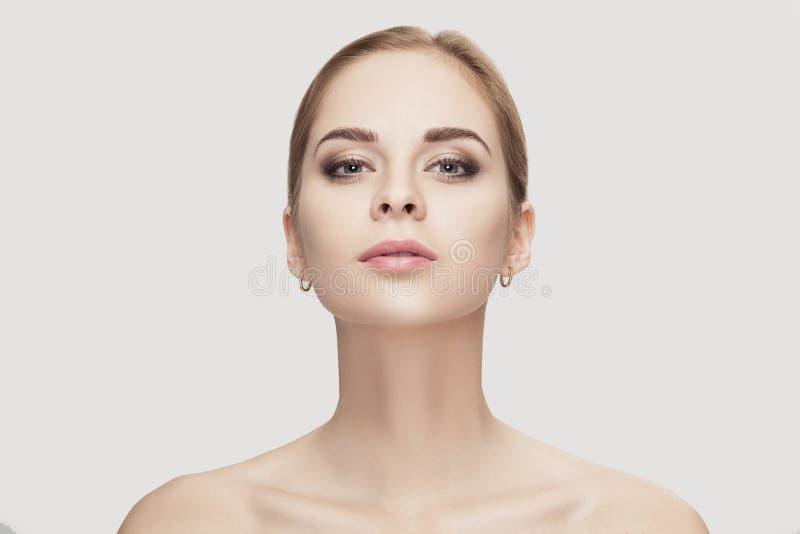 Voorportret van mooie jonge vrouw met groene ogen op grijze close-up als achtergrond Meisje met schone huid stock afbeelding