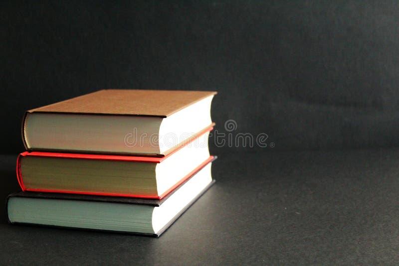 Voorraad van boeken in harde dekking, zwarte achtergrond, vrije exemplaarruimte stock foto