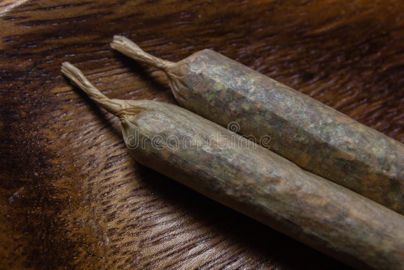 Voorraad van hand - gemaakte marihuanaverbindingen op houten schotel stock foto's