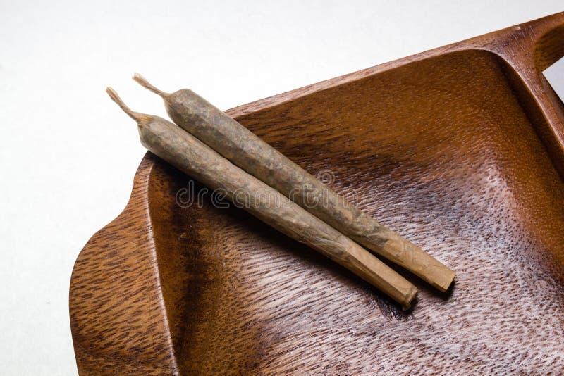 Voorraad van hand - gemaakte marihuanaverbindingen op houten schotel stock fotografie