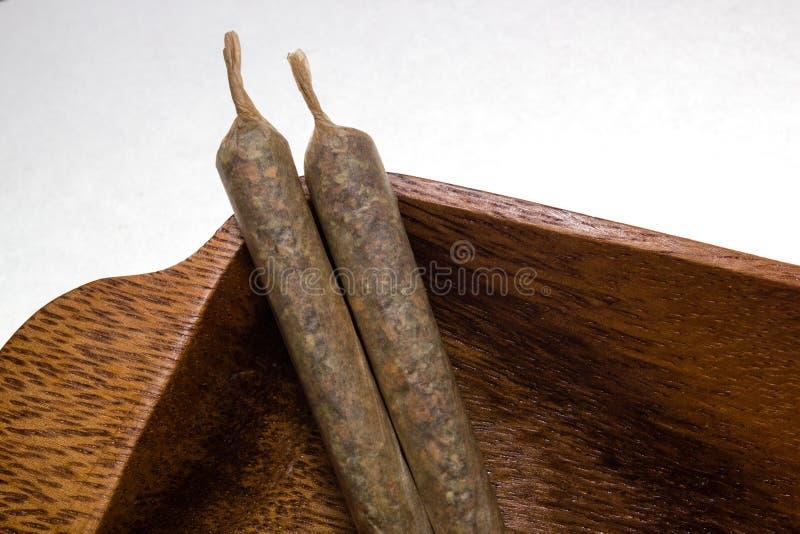 Voorraad van hand - gemaakte marihuanaverbindingen op houten schotel stock foto