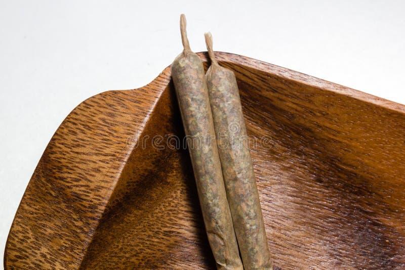 Voorraad van hand - gemaakte marihuanaverbindingen op houten schotel royalty-vrije stock afbeelding