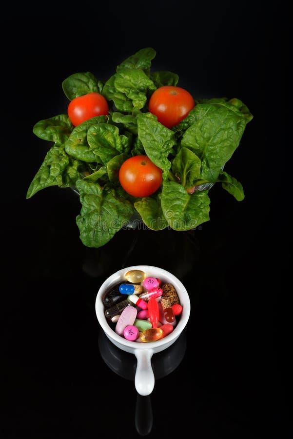 Voorschriftpillen en de Drugs van het Geneeskundemedicijn tegenover Spinaziesalade stock afbeelding