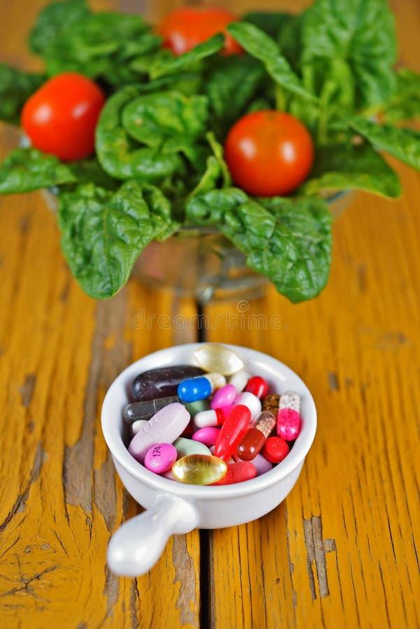 Voorschriftpillen en de Drugs van het Geneeskundemedicijn tegenover Spinaziesalade royalty-vrije stock afbeeldingen