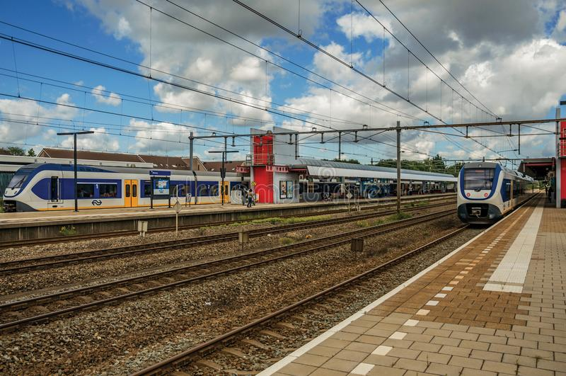 Voortbewegingseinde op stationplatform, spoorwegsporen en blauwe bewolkte hemel in Weesp stock fotografie