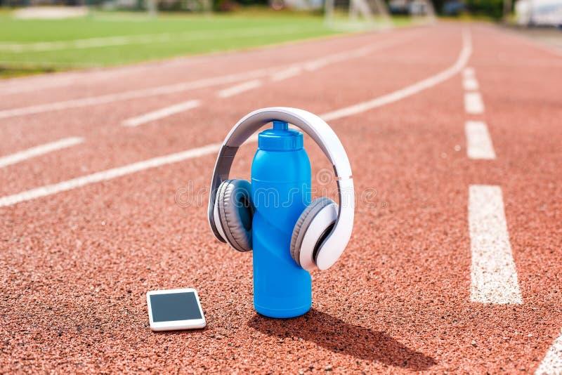 Voorwerpen op de hoofdtelefoons van het stadionspoor op fles van water en smartphoneclose-up royalty-vrije stock foto's