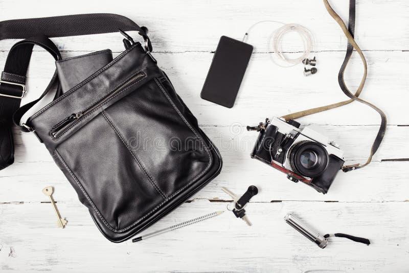 Voorwerpen op houten achtergrond: leerzak, camera, smartphone, sleutels, flitslicht Uitrusting van stedelijke reiziger stock afbeeldingen