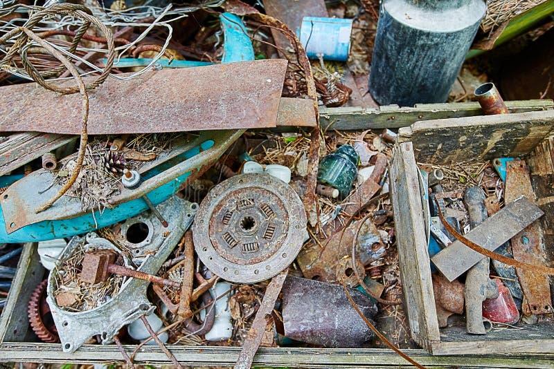 Voorwerpen van het stortplaats de oude metaal in het hout, roestige schroot omgeef royalty-vrije stock foto