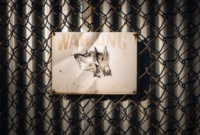 Voorzichtig zijn van het teken van de wachthond op de omheining van de kettingsverbinding stock fotografie