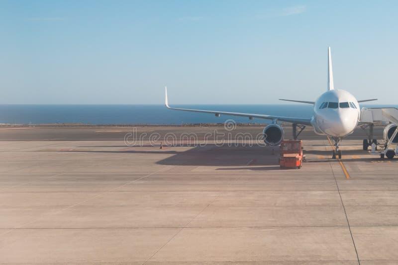 Voorzijde die van vliegtuig zich op baan met oceaanachtergrond bevinden stock fotografie