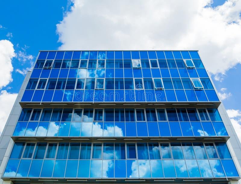 Voorzijde van een modern gebouw De glasvensters wezen op de hemel en de wolken blauwe gamma royalty-vrije stock foto