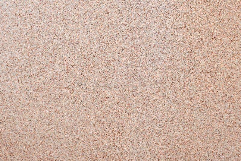 Vor dem hintergrund des verbreiteten kleinen Kieses des Sandes eine Steinkrume Beschaffenheit einer Oberfläche einer Wand, helle  stockbilder