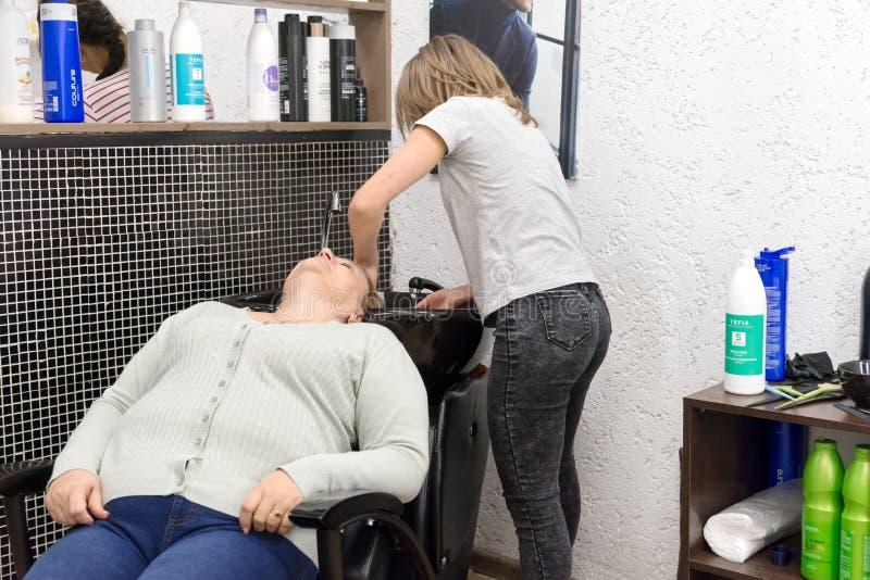 Vor dem Schnitt in eine spezielle Wanne im Salon des Friseurs im wirklichen workin weiblicher Friseur wäscht den Kopf der Kundenf stockbilder