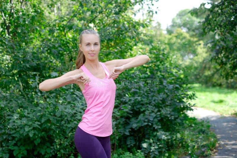 Vor der Ausbildung das Porträt der sportlichen Frau das Ausdehnen tuend trainiert im Park Weiblicher Athlet, der für das Rütteln  stockbilder