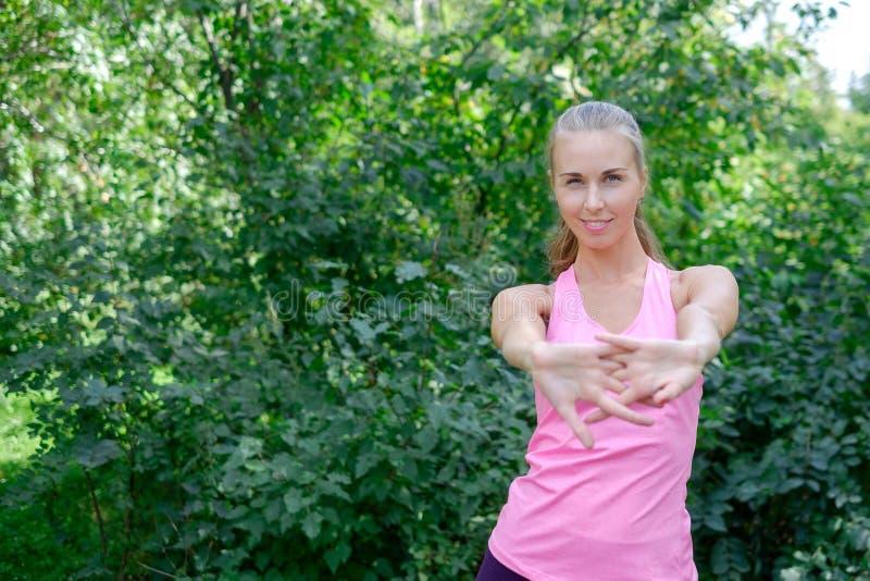 Vor der Ausbildung das Porträt der sportlichen Frau das Ausdehnen tuend trainiert im Park Weiblicher Athlet, der für das Rütteln  lizenzfreies stockbild