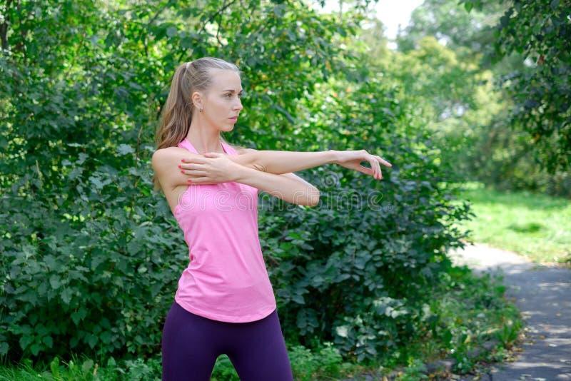 Vor der Ausbildung das Porträt der sportlichen Frau das Ausdehnen tuend trainiert im Park Weiblicher Athlet, der für das Rütteln  stockfoto