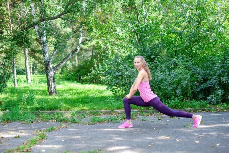 Vor der Ausbildung das Porträt der sportlichen Frau das Ausdehnen tuend trainiert im Park Weiblicher Athlet, der für das Rütteln  stockfotos