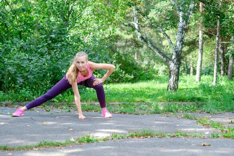 Vor der Ausbildung das Porträt der sportlichen Frau das Ausdehnen tuend trainiert im Park Weiblicher Athlet, der für das Rütteln  lizenzfreie stockfotos