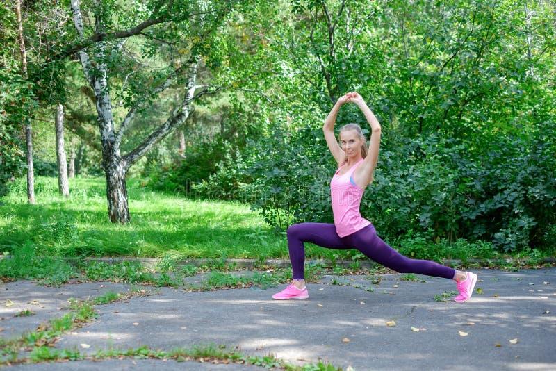 Vor der Ausbildung das Porträt der sportlichen Frau das Ausdehnen tuend trainiert im Park Weiblicher Athlet, der für das Rütteln  lizenzfreies stockfoto