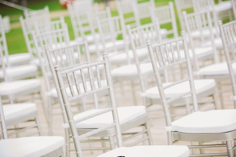 Vor einer Hochzeitszeremonie endlose weiße Stühle stockfotografie