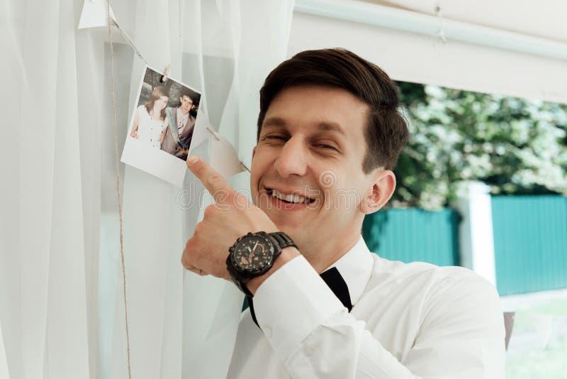 Vor hübscher stilvoller Bräutigam, der erstes altes Foto mit seiner Braut langer Zeit, emotionaler Spaßmoment betrachtet lizenzfreies stockbild