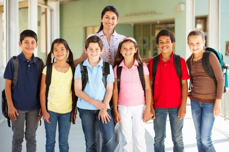 Vor jugendlich Schulkinder mit Lehrer lizenzfreie stockfotografie
