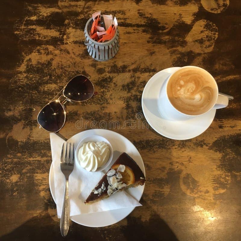 Vor Schuss-Draufsicht des orange Mohn-Kuchens und des Kaffees im Café stockfoto
