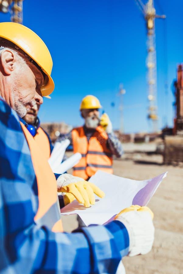 Vorarbeiter, der einen Bauplan bei der Stellung an der Baustelle prüft lizenzfreie stockfotografie