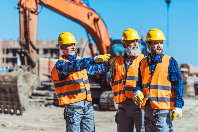 Vorarbeiter, der Erbauern etwas an der Baustelle durch das Zeigen seins zeigt lizenzfreie stockfotos