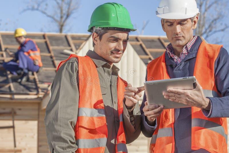 Vorarbeiter und Laie auf Baustelle lizenzfreie stockfotografie