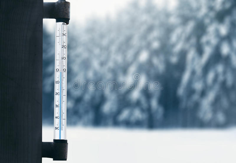 Voraussage und Winter verwittern Jahreszeit, Thermometer auf Glasfenster mit unscharfem Hintergrund des verschneiten Winters Wald lizenzfreie stockfotografie