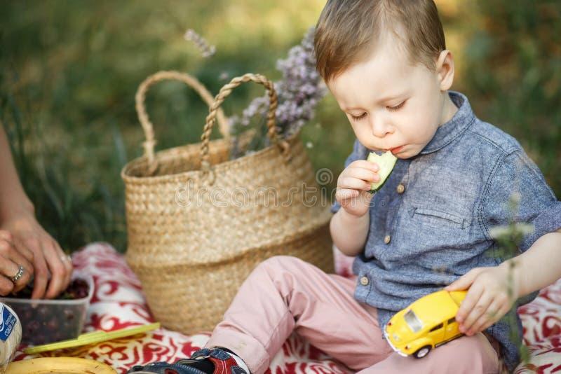 Vorbei sitzt auf Decke und spielt mit Spielzeug Er hat gelbes Auto auf seinem Haar Auch Kind isst lizenzfreie stockfotos