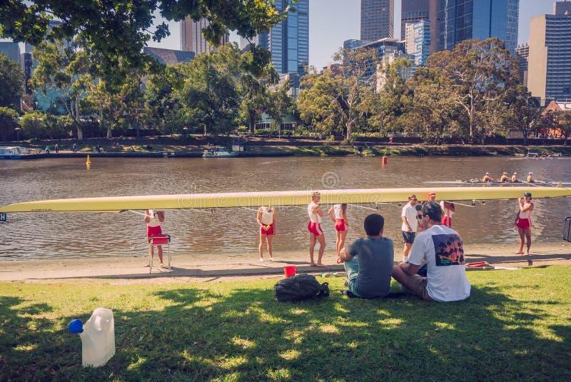 Vorbereiten des Ruderboots auf dem Fluss durch Teammitglied lizenzfreie stockbilder