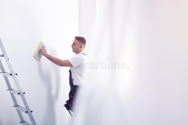 Vorbereitende weiße Wand der Arbeitskraft nahe bei Leiter während der Haupterneuerung stockfotos
