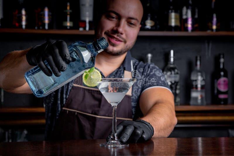 Vorbereitendes und strömendes Cocktail des Kellners in Martini-Klasse stockbilder