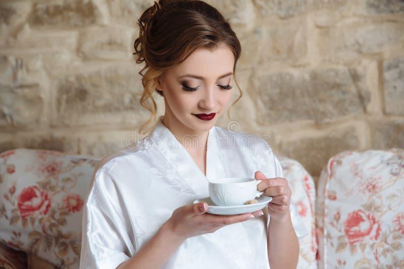 Vorbereitung der Braut am Hochzeitstag Ein Mädchen mit einem Tasse Kaffee betrachtet die Pläne für heute Eine Frau isst lizenzfreie stockbilder