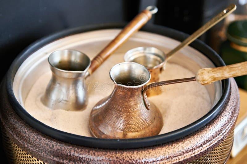 Vorbereitung des türkischen Kaffees im cezve im Sand lizenzfreies stockfoto