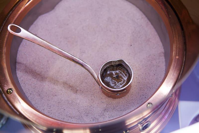 Vorbereitung des türkischen Kaffees im cezve im Sand stockfotografie