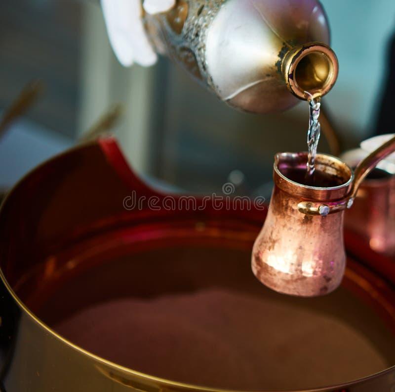 Vorbereitung des türkischen Kaffees im cezve im Sand an der Cafébar stockfoto
