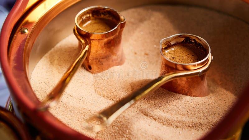 Vorbereitung des türkischen Kaffees im cezve im Sand an der Cafébar lizenzfreie stockfotos