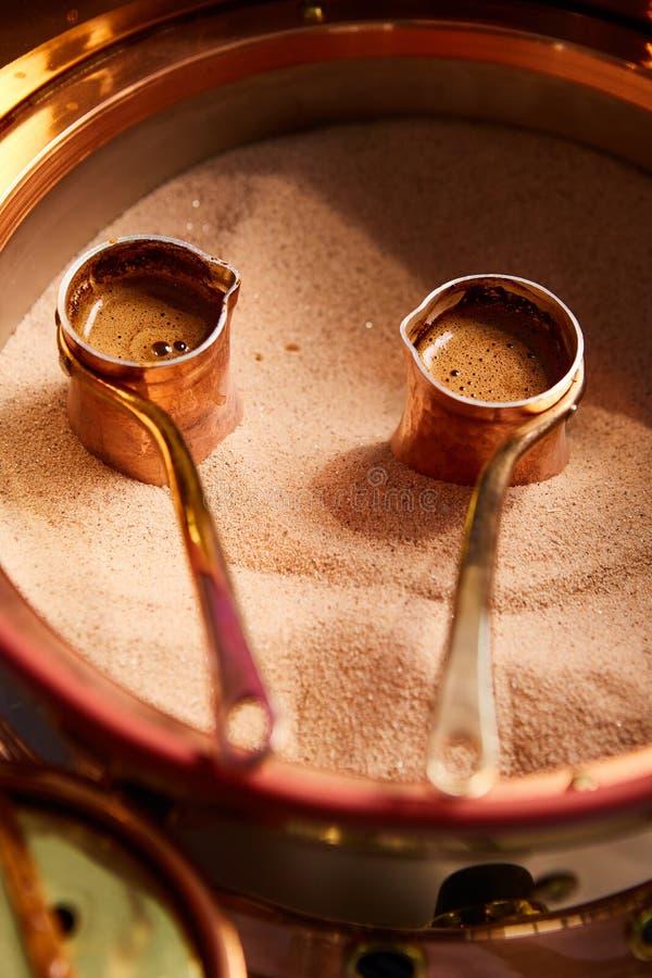 Vorbereitung des türkischen Kaffees im cezve im Sand an der Cafébar stockfotos