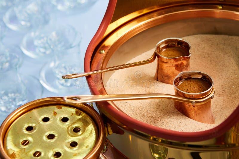 Vorbereitung des türkischen Kaffees im cezve im Sand an der Cafébar lizenzfreies stockfoto