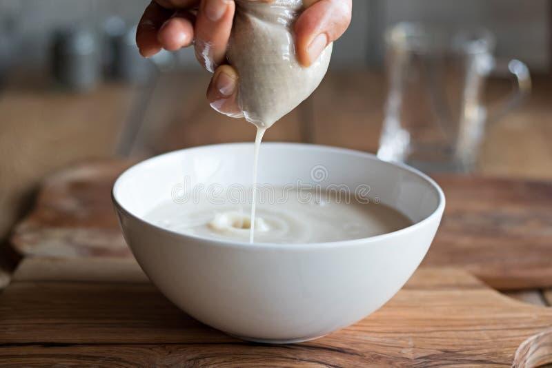 Vorbereitung von Nussmilch - Belasten der Milch durch eine Milchtasche lizenzfreies stockfoto