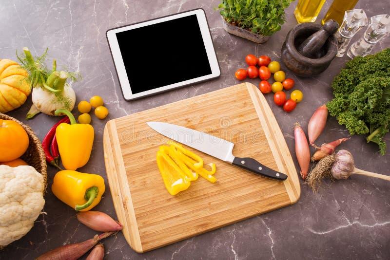 Vorbereitungstabelle in der Küche für das Kochen mit Tablette stockfotografie