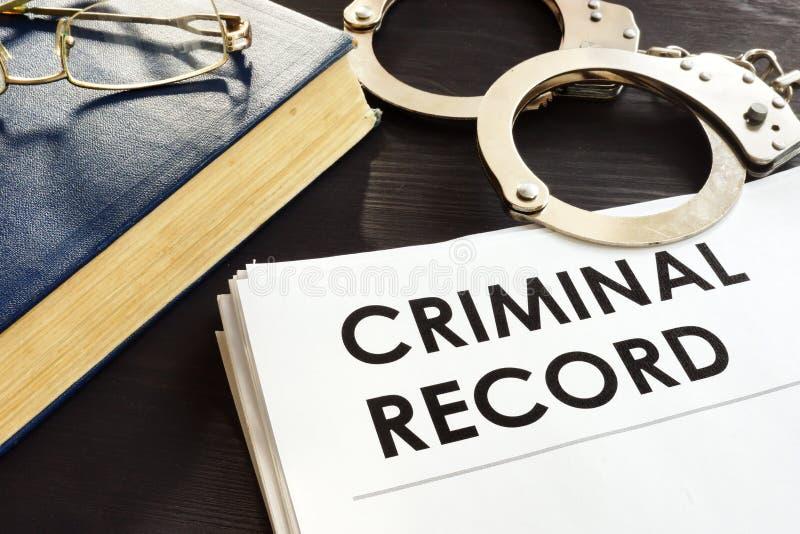 Vorbestrafung und Handschellen auf einem Schreibtisch stockfotos