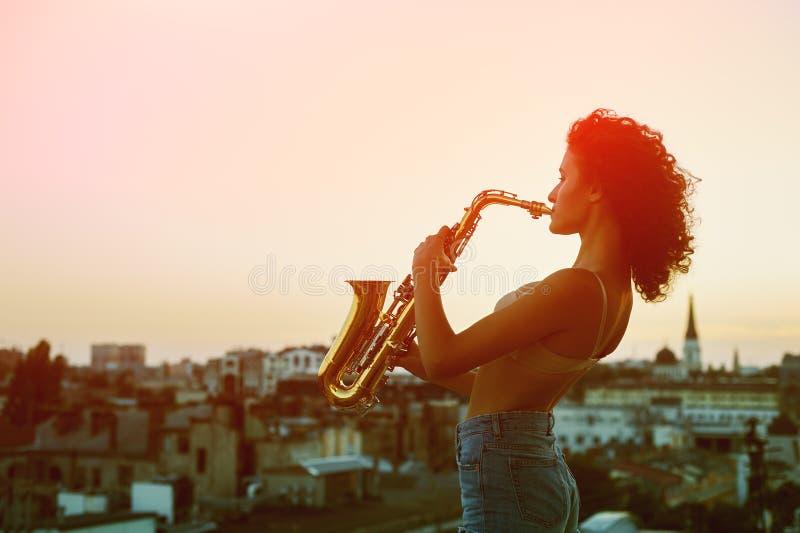 Vorbildliche Aufstellung der jungen Frau auf dem Dach des Gebäudes, das ein Saxophon hält lizenzfreies stockfoto